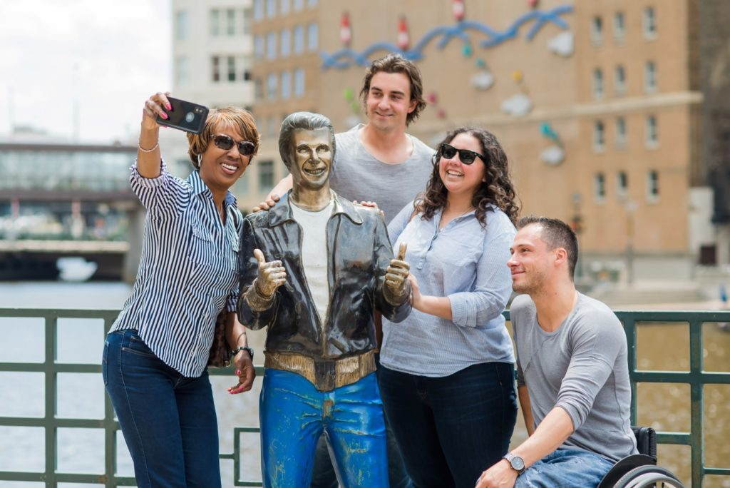 tourists taking a selfie with Fonzie statue
